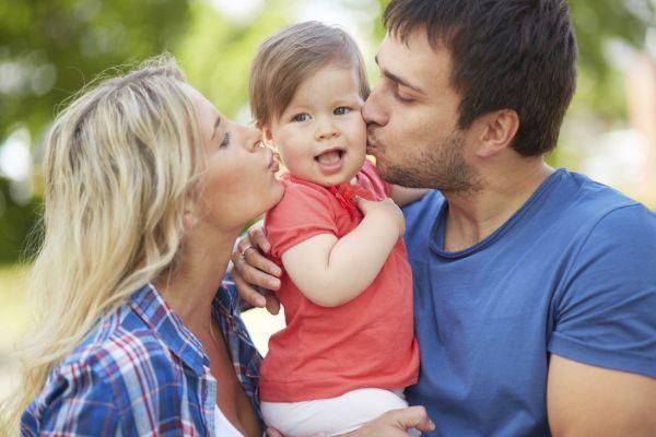 женщина и мужчина целуют ребенка