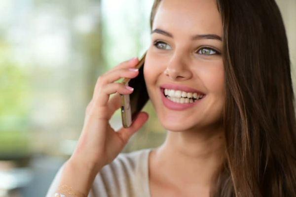 девушка радостно говорит по телефону